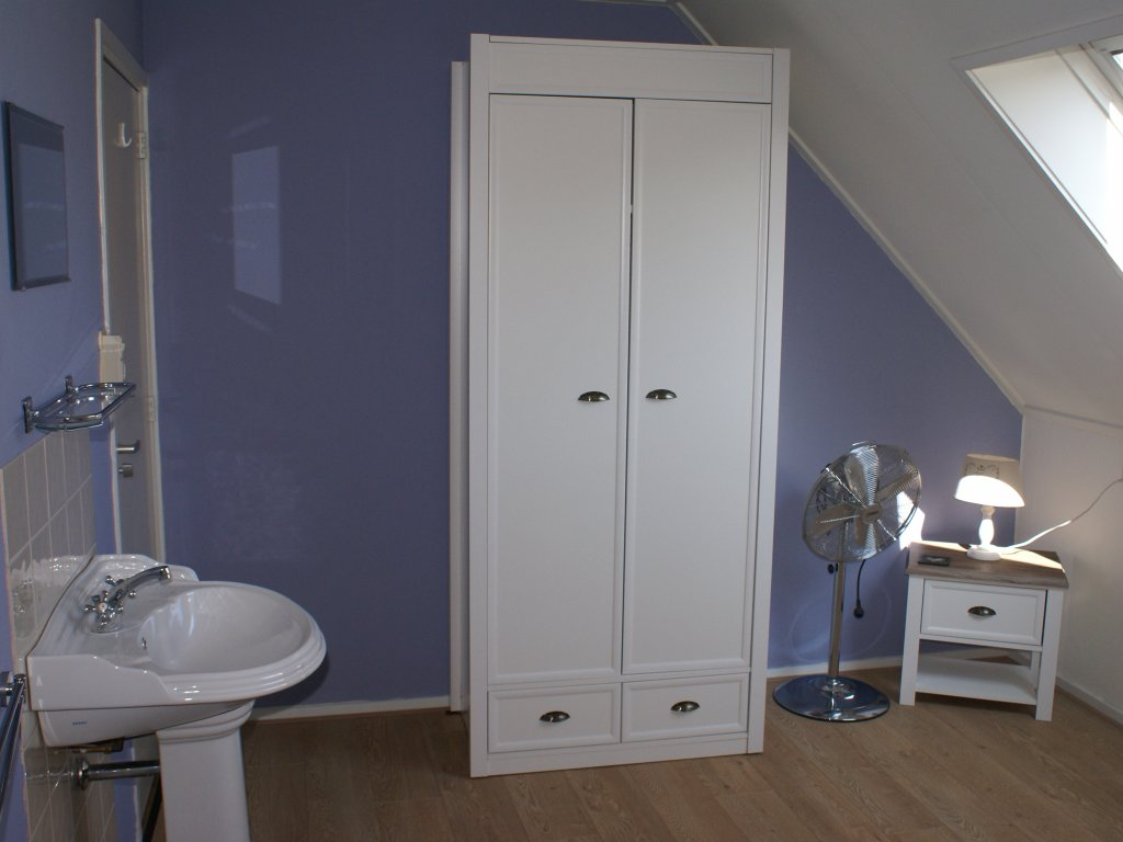 One of the twin bedrooms with basin and a wardrobe
